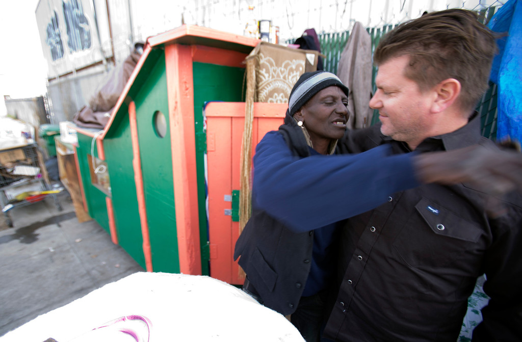 """. \""""Wonder,\"""" a homeless woman who now lives in on the street in west Oakland, Calif., hugs Greg Kloehn, a local man who takes discarded building materials and turns them into rolling shelters, Tuesday, Dec. 31, 2013. (D. Ross Cameron/Bay Area News Group)"""