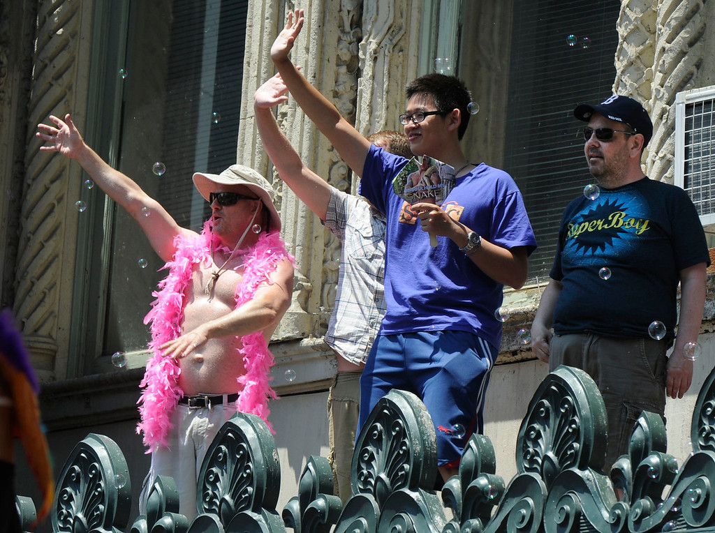 . From atop the marquee of the Orpheum Theatre, people wave down to the participants in the 42nd San Francisco Pride Celebration and Parade in San Francisco, Calif., on Sunday, June 30, 2013. (Susan Tripp Pollard/Bay Area News Group)