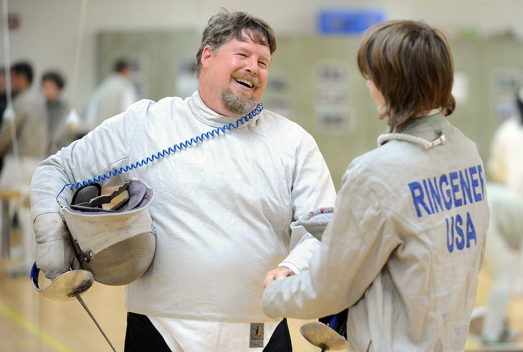 . Saber instructor Jim Ringener, of Hayward, left, shakes hands with student Ian Sterling, of Pleasanton, after a saber match during the Las Positas Fencing Center\'s Level II Saber class for adults held at Las Positas College in Livermore, Calif., on Tuesday, July 9, 2013. The fencing center is operated through the Las Positas College Community Education program and offers instruction in foil, epee and saber. The center offers classes in all levels of fencing for adults and children over the age of 8. (Doug Duran/Bay Area News Group)