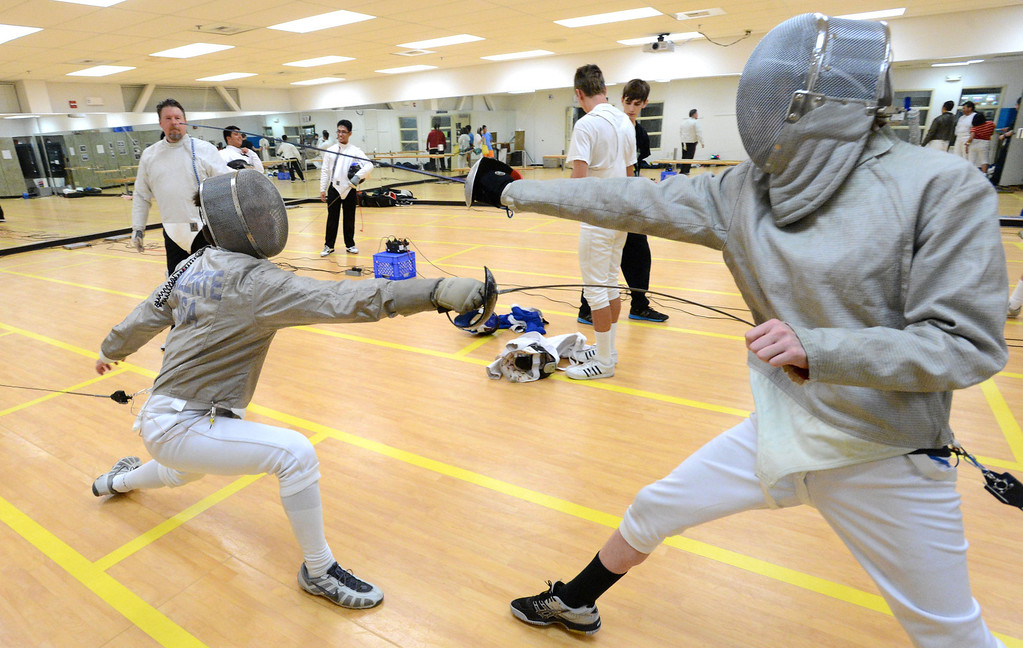 . Michael Valente, of Danville, left, and Ian Sterling, of Pleasanton, have a saber match during the Las Positas Fencing Center\'s Level II Saber class for adults held at Las Positas College in Livermore, Calif., on Tuesday, July 9, 2013. The fencing center is operated through the Las Positas College Community Education program and offers instruction in foil, epee and saber. The center offers classes in all levels of fencing for adults and children over the age of 8. (Doug Duran/Bay Area News Group)
