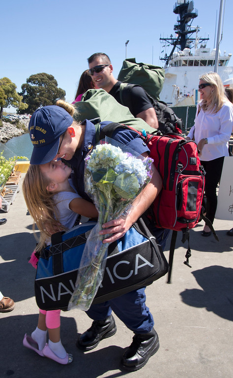 . U.S. Coast Guard Electronics Technician Ruth Ford, center, hugs her 4-year-old daughter, Naomi, as she returns to Coast Guard Island after a 160-day deployment aboard the USCG Cutter Bertholf on Thursday, Sept. 5, 2013, in Alameda, Calif. (D. Ross Cameron/Bay Area News Group)