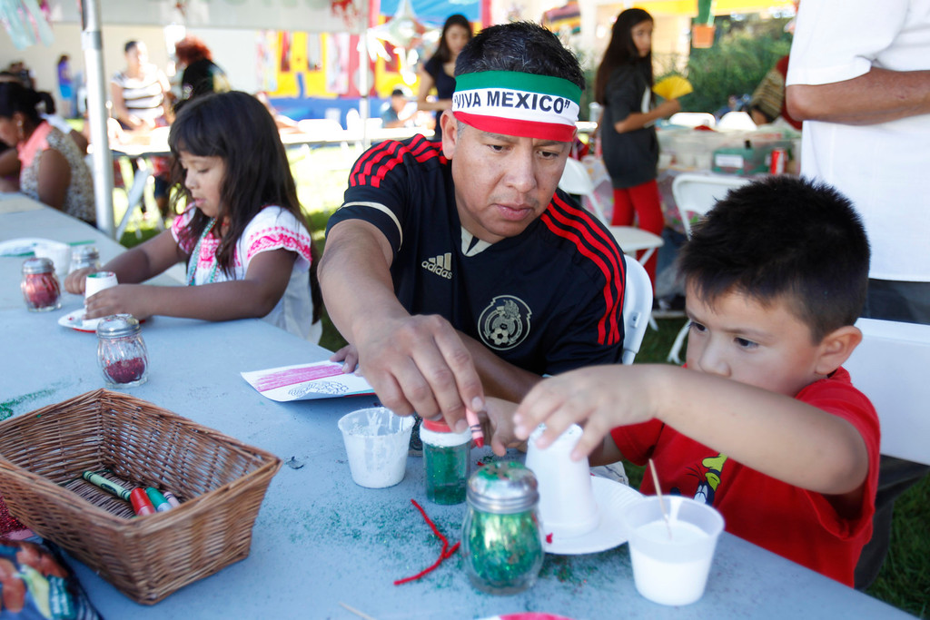 . Miguel Mestizo, center, helps his son Luis Miguel Mestizo, 4, with an arts project at the arts and culture community booth at the ¡VivaFest!/El Grito music and cultural festival event celebrating Mexico�s Independence Day at Discovery Meadow in San Jose, Calif., on Sunday, Sept. 15, 2013. Brianna Garcia, 6, is at left. (Josie Lepe/Bay Area News Group)