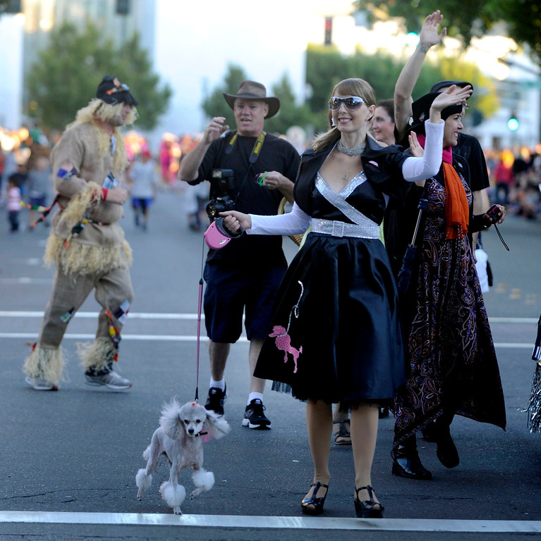 . With her poodle skirt and poodle named Pierre, Dasha O\'Bolenskaya of Walnut Creek waves to the crowd along Main Street at the Walnut Festival Twilight Parade in Walnut Creek, Calif., on Saturday, Sept. 14, 2013.  (Susan Tripp Pollard/Bay Area News Group)