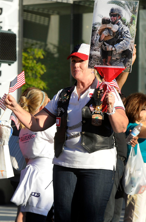 . Blue Star mom Jana Clark of Concord hands out American flags at the Walnut Festival Twilight Parade in Walnut Creek, Calif., on Saturday, Sept. 14, 2013. Her son Josh Clark has served four tours in the Army. (Susan Tripp Pollard/Bay Area News Group)