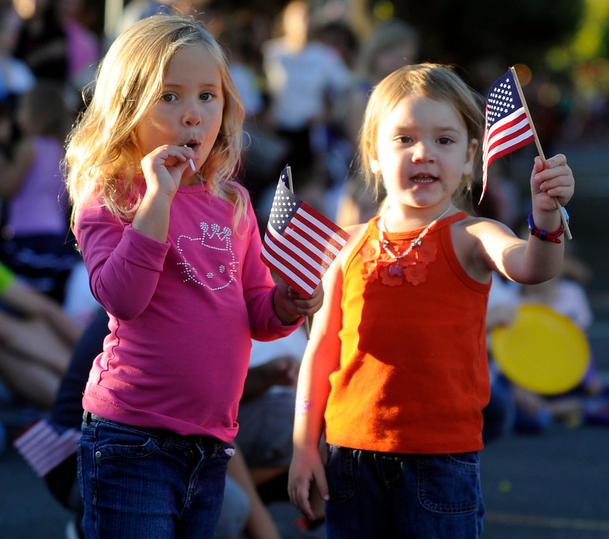 . Best friends Evelyn Canova, 3, and Kate Hodge watch the Walnut Festival Twilight Parade in Walnut Creek, Calif., on Saturday, Sept. 14, 2013.  (Susan Tripp Pollard/Bay Area News Group)