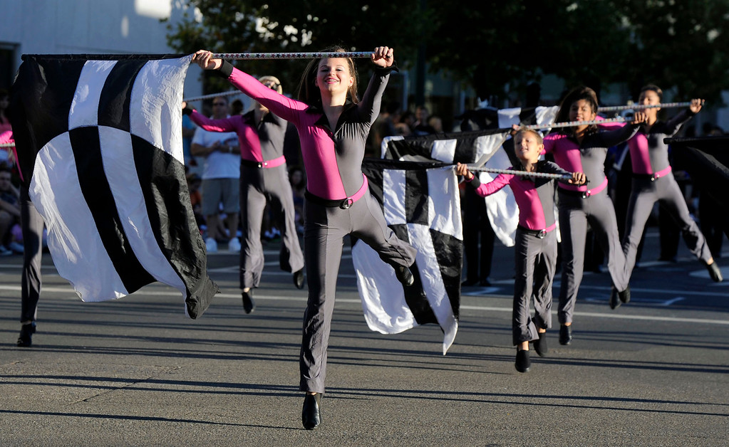 . Members of the Concord Blue Devils color guard perform in the Walnut Festival Twilight Parade in Walnut Creek, Calif., on Saturday, Sept. 14, 2013.  (Susan Tripp Pollard/Bay Area News Group)
