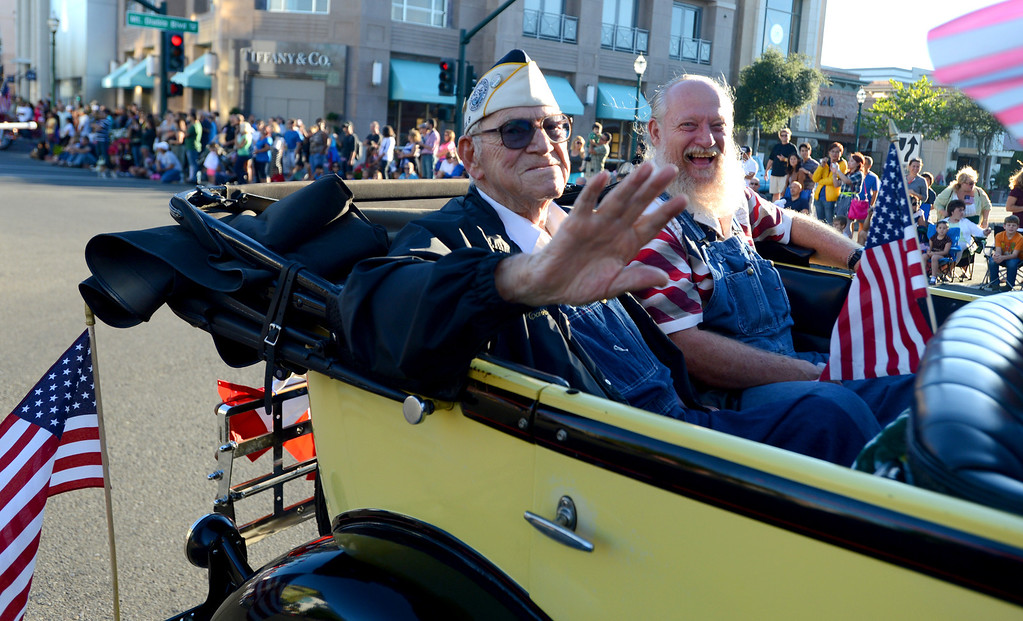 . Pearl Harbor Survivor Hank Fries, 93, of Bay Point waves to the crowd as he rides in the back of a classic convertible along Main Street with his son Calvin Fries at the Walnut Festival Twilight Parade in Walnut Creek, Calif., on Saturday, Sept. 14, 2013.  (Susan Tripp Pollard/Bay Area News Group)