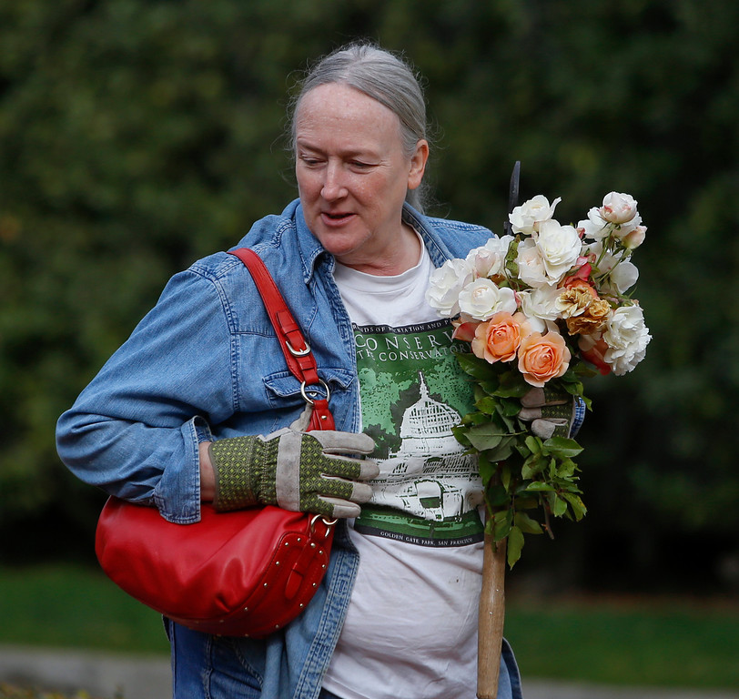 . Volunteer Normandie Ross takes home a bundle of roses after a day of pruning in Central Park. (John Green/Bay Area News Group)