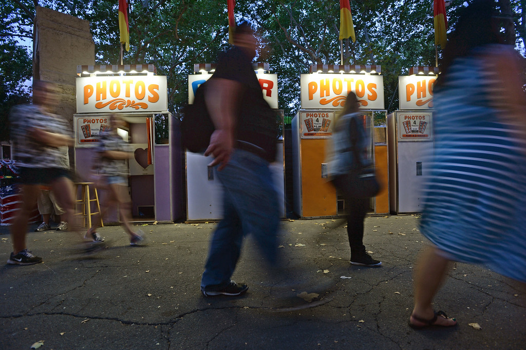 . Fairgoers walk past a line of photo booths at the Alameda County Fair on June 20, 2014. (Doug Duran/Bay Area News Group)