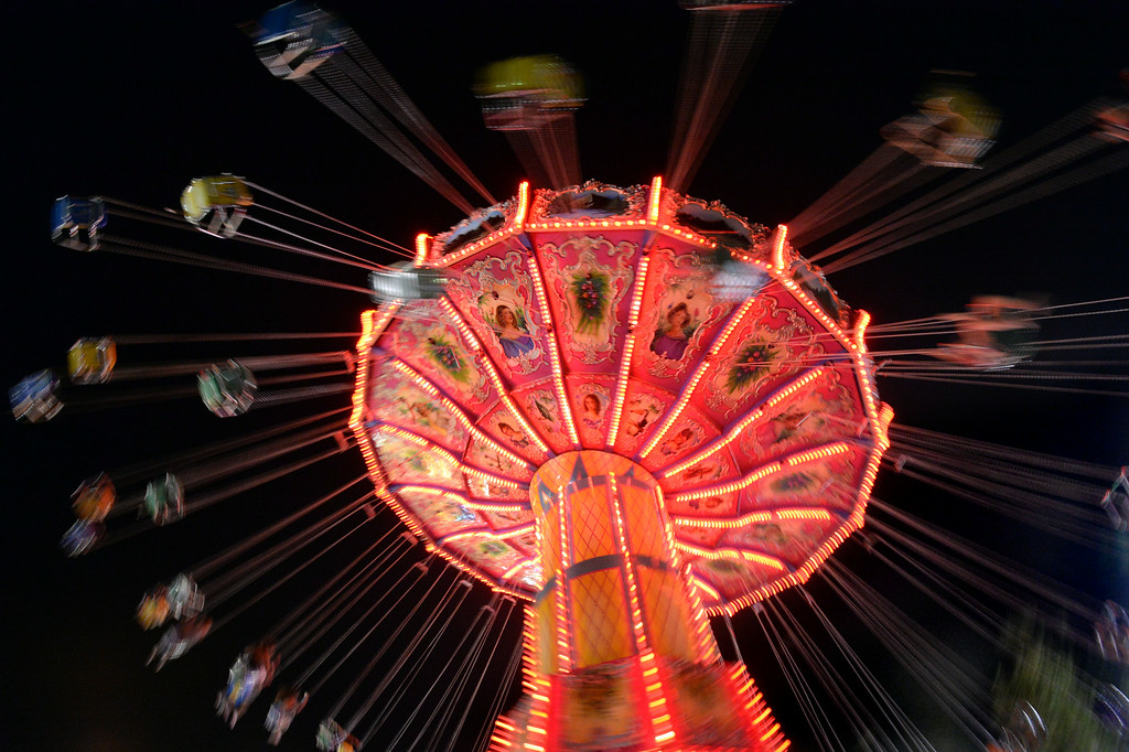 . Fairgoers swing through the air on the Wave Swinger carnival ride as it tilts from side to side at the Alameda County Fair in Pleasanton, Calif., on Friday, June 20, 2014. (Doug Duran/Bay Area News Group)
