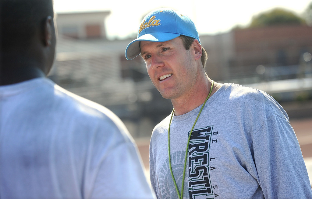 . De La Salle High\'s new head football coach Justin Alumbaugh, talks to a member of his team during practice in Concord, Calif., on Tuesday, Aug. 6, 2013. Alumbaugh takes over the state\'s most elite high school football program from the reins of the legendary Bob Ladouceur, who retired this spring after 33 years. (Doug Duran/Bay Area News Group)