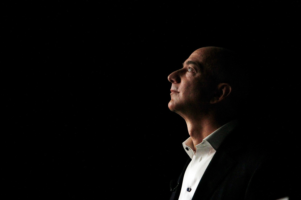. Jeff Bezos, CEO and founder of Amazon, is illuminated by a display screen at the introduction of the new Amazon Kindle Fire HD and Kindle Paperwhite in Santa Monica, Calif., Thursday, Sept. 6, 2012. (AP Photo/Reed Saxon)