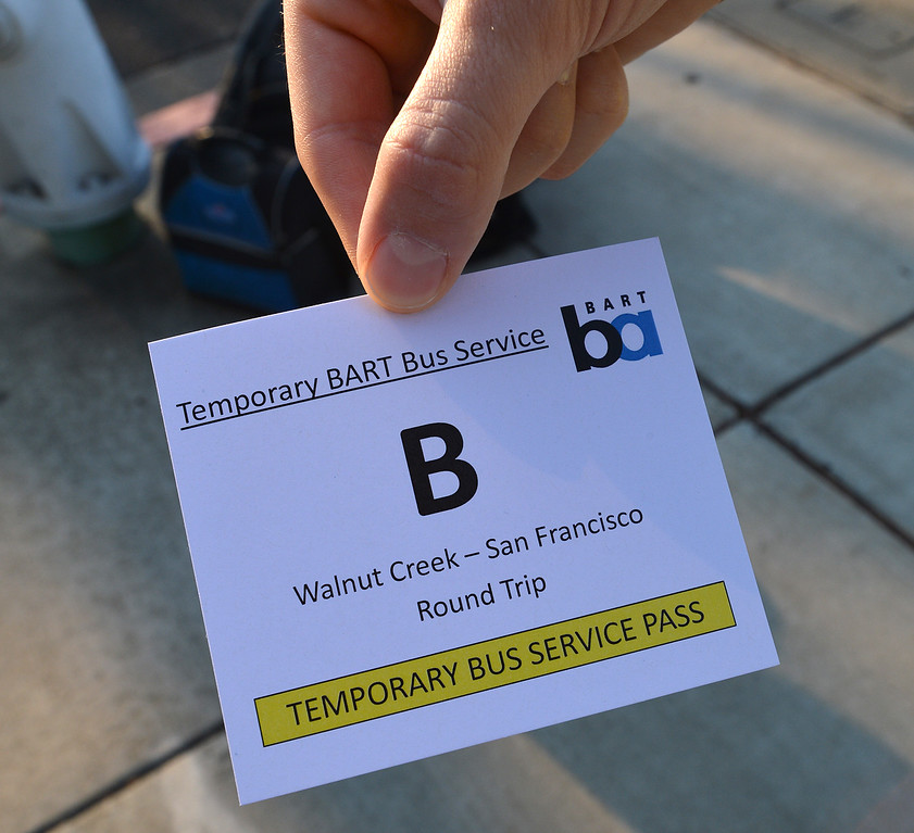 . A ticket is given to each person as they enter a bus on California Boulevard to take them to San Francisco on the second day of the BART strike in Walnut Creek, Calif., on Tuesday, July 2, 2013.  (Dan Rosenstrauch/Bay Area News Group)
