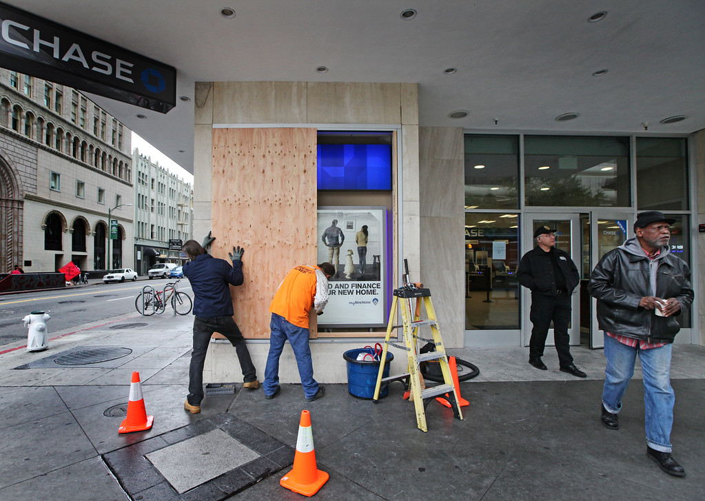 . Workers begin the process of boarding up the broken windows at Chase  Bank on Broadway in Oakland, Calif., Monday, July 15, 2013, as security monitors the front entrance. Downtown Oakland merchants are once again cleaning up after a weekend of protest and late night violence. (Laura A. Oda/Bay Area News Group)