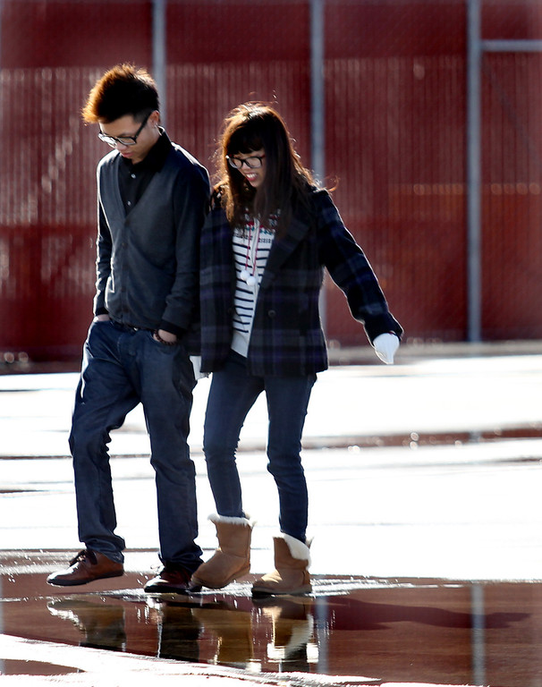 . Laney College students Zhexian Hunn, left, and Theresa Wang walk through a rain puddle during a visit at Alameda Point in Alameda, Calif., on Tuesday, Feb. 19, 2013. (Ray Chavez/Staff)