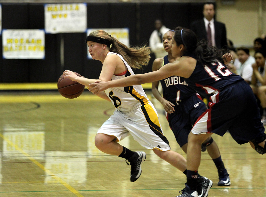 . Alameda\'s Maddy Lewis (15) drives past Dublin\'s Milan Moses (1) and Alison Martinez (12) in the first half of a North Coast Section Division II quarterfinal playoff game at Alameda High in Alameda, Calif., on Friday, Feb. 22, 2013.  (Ray Chavez/Staff)