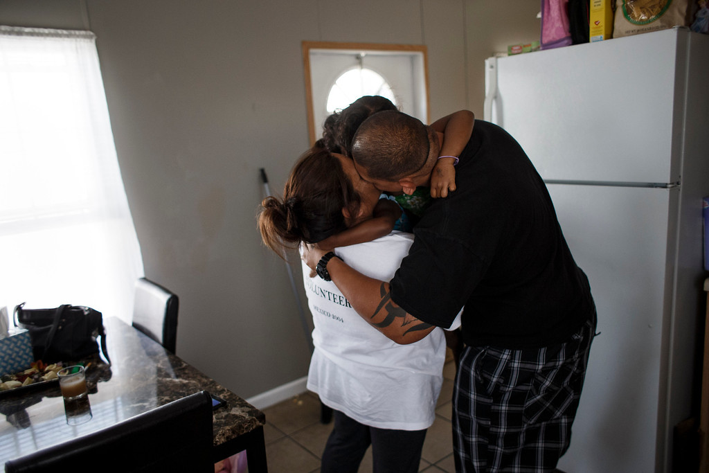 . Clarissa Taitano and her partner, Mike Finona, hug Taitano\'s daughters, A\'Riyah Jackson, 5, and I\'Yannah Jackson, 3, in their mobile home on May 24, 2013, in San Jose. The family recently moved to their mobile home after living in a Santa Clara motel for 64 days. (Dai Sugano/Bay Area News Group)