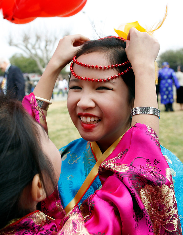. From left, Stars Dance Team member Jenny Trieu, 8, puts beads on fellow team member Kathy Nguyen,10, before they perform at the Tet festival hosted by the Coalition of Nationalist Vietnamese Organizations of Northern California (CONVONCA) at the Santa Clara County Fairgrounds in San Jose, Calif. on Saturday, February 2, 2013.   (LiPo Ching/Staff)