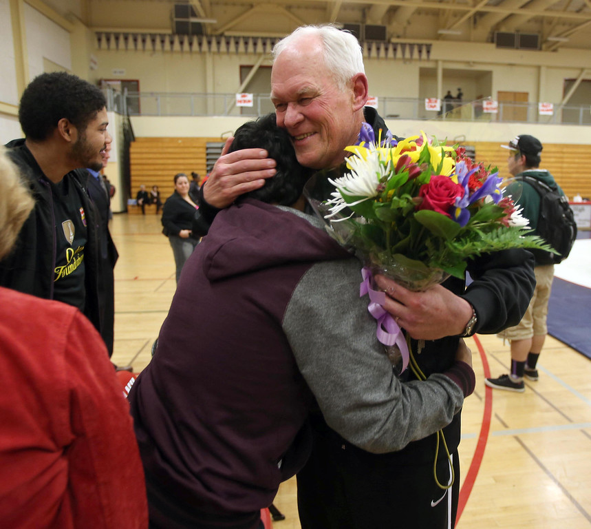 . Albany High School wrestling coach Kermit Bankson, right, gets a hug from alumni Daniel Singh, 23, of Berkeley, after their match against Tennyson High School in Albany, Calif. on Friday, Jan. 17, 2013. Bankson is retiring after coaching the Cougars for 43 years, and this was his last match. (Jane Tyska/Staff)