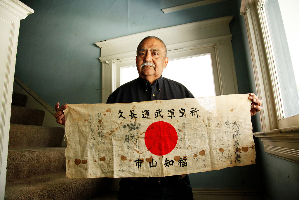 . Charley Trujillo holds the Japanese flag his father, Raymond Trujillo, captured from a dead Japanese soldier in New Guinea in 1943, at his home in San Jose on Thursday, May 17, 2012.   Raymond Trujillo was a Private, First Class in the U.S. Army during World War II. Charley Trujillo is working to return the flag to the surviving relatives of the Japanese military who signed the flag. (LiPo Ching/Staff)
