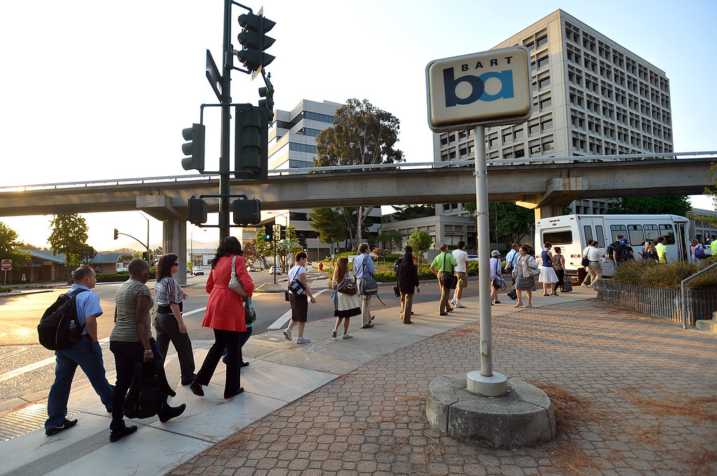 . A long line of commuters work their way down California Boulevard to a line of buses waiting to take them to San Francisco on the second day of the BART strike in Walnut Creek, Calif., on Tuesday, July 2, 2013.  (Dan Rosenstrauch/Bay Area News Group)