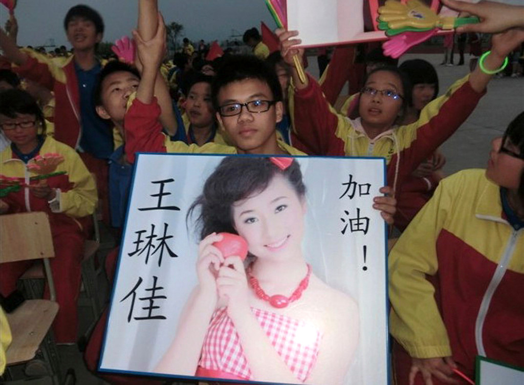 . In this undated photo made available Monday, July 8, 2013, a supporter of Wang Linjia, holds up a photo of her with her name during a talent show at a school in Jiangshan city in eastern China\'s Zhejiang province. Chinese state media and Asiana Airlines have identified the two victims of the Asiana Airlines crash at San Francisco International Airport girls as Ye Mengyuan and Wang Linjia, students in Zhejiang, an affluent coastal province in eastern China.  (AP Photo)