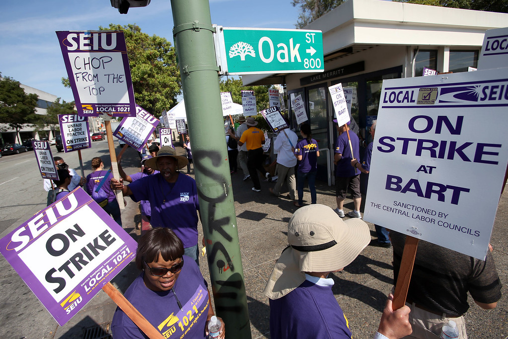 . BART employees represented by the Service Employees International Union Local 1021 picket in front of the Lake Merritt BART station in Oakland, Calif., on Wednesday, July 3, 2013. The BART strike is in its third day and bargaining talks will resume at 1 p.m. Wednesday. (Jane Tyska/Bay Area News Group)