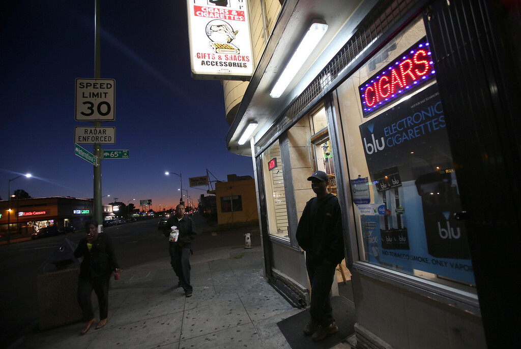 """. One Stop Smoke Shop owner Abdelbain Abdelkadir, right, stands outside his store at 65th Avenue in Oakland, Calif., on Wednesday, April 17, 2013. \""""It\'s like any other city, it has its good and bad sides. It\'s a beautiful city, but the kids have nothing to do here,\"""" Abdelkadir said. (Jane Tyska/Staff)"""