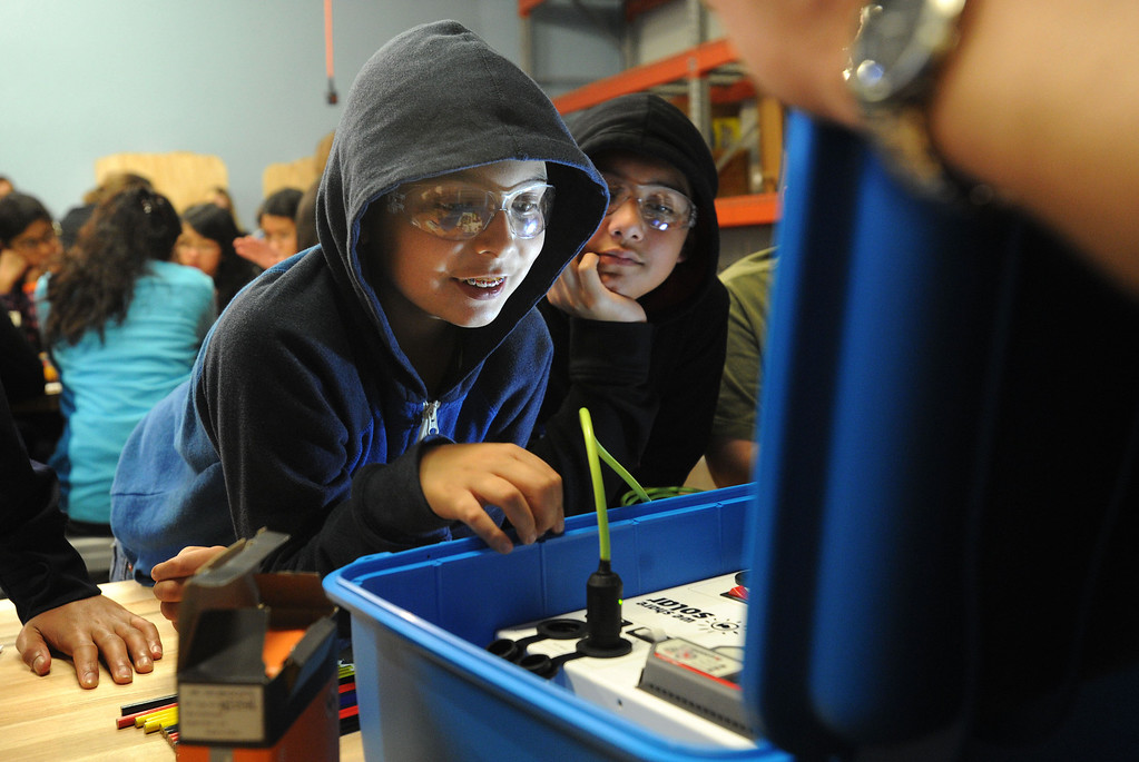 . Andres Leal, left, and Luis Merino, both 11 and of San Jose, smile as they plug in a light to test a solar suitcase at the Tech Museum in San Jose, Calif., on Monday, Jan. 21, 2013. As part of Martin Luther King Jr.\'s legacy of service, young students from around the Bay Area took part in the assembling of WE CARE (Women\'s Emergency Communication and Reliable Electricity) solar suitcases. These suitcases contain a complete solar electric system that will be sent to Sierra Leone. (Dan Honda/Staff)