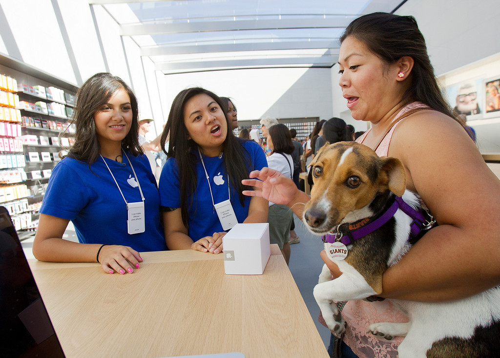 . Rhian Poblete, right, with her dog Keno, speaks to Apple Family Room Specialists Joy Edquilang (center) and Jessica Barron (left) at the redesigned Apple Store at the Stanford Shopping Center in Palo Alto, Calif., on Saturday, Sept. 7, 2013.  (LiPo Ching/Bay Area News Group)
