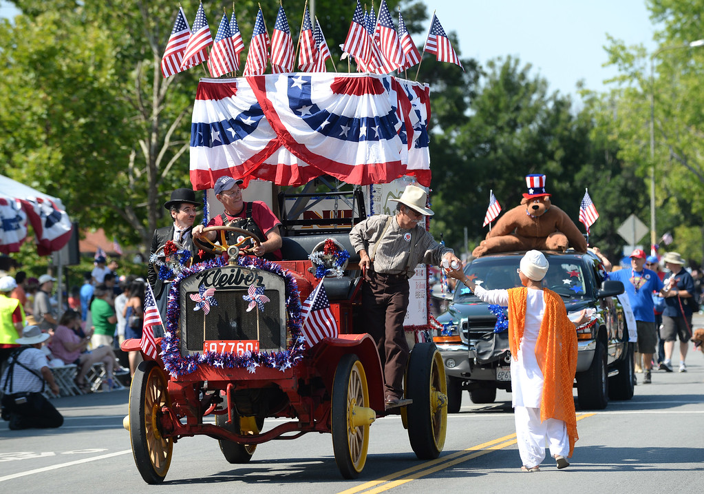 . Malinder Kaur, of the Sikh Community of the Bay Area, right, hands water to parade participants, including a Charlie Chaplin impersonator, far left, at the Fourth of July parade in Fremont, Calif., on Thursday, July 4, 2013. The parade featured more than 70 entries. (Dan Honda/Bay Area News Group)