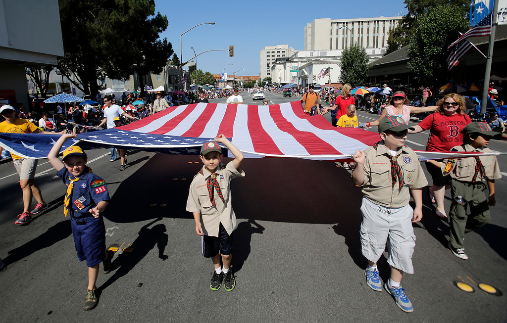. Members of Cub Scout Troop 991carry the American flag during the annual Fourth of July parade in Redwood City, Calif. on Thursday, July 4, 2013. Considered the largest Independence Day parade in Northern California, it is celebrating its 75th year. (Gary Reyes/Bay Area News Group)
