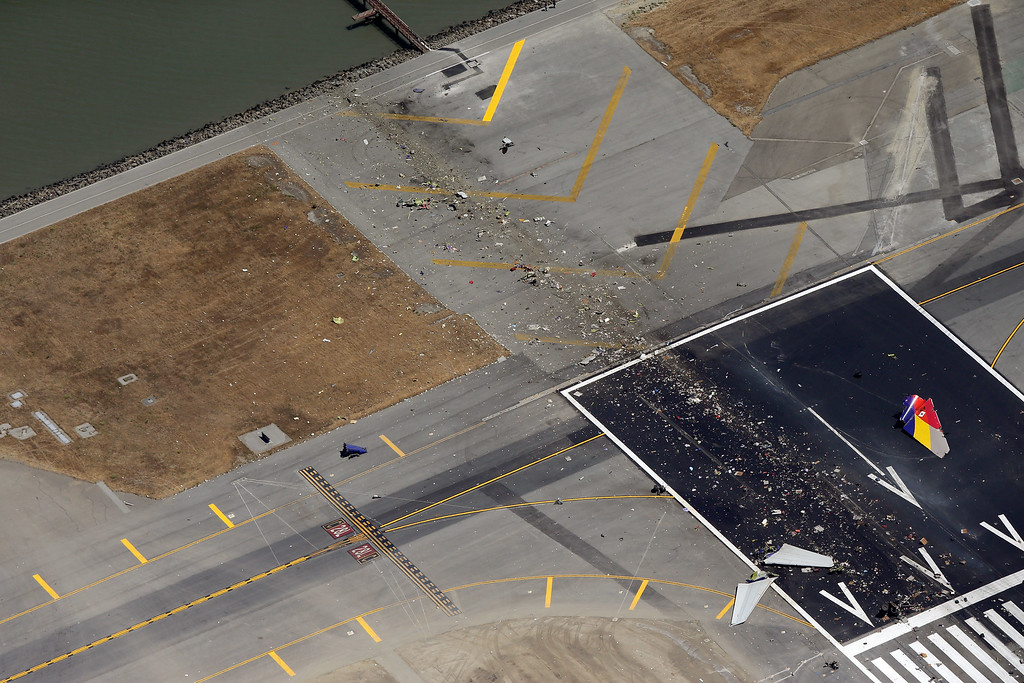 . A close-up of the runway and debris of a Boeing 777 airplane that burned on the runway after it crash landed at San Francisco International Airport July 6, 2013 in San Francisco, California. An Asiana Airlines passenger aircraft coming from Seoul, South Korea crashed while landing. There has been at least two casualties reported. (Photo by Ezra Shaw/Getty Images)