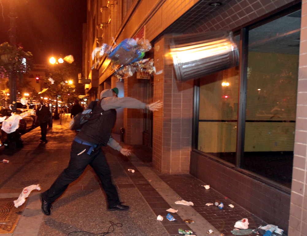 . A man throws a trash can at the window of a building along Broadway near Telegraph Avenue during a protest march in Oakland, Calif., early Sunday, July 14, 2013. Protesters marched through the city with some in the group smashing windows, spraying graffiti and setting fires after learning that George Zimmerman had been found not guilty in the shooting death of Trayvon Martin. (Anda Chu/Bay Area News Group)
