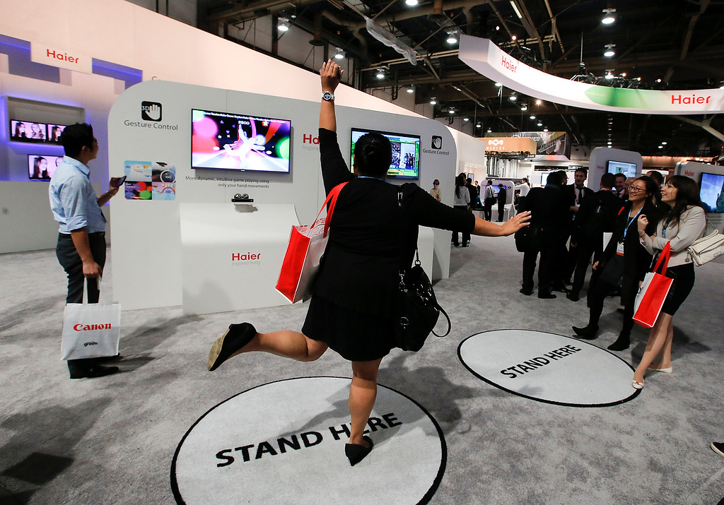 . A show attendee tries out Haier\'s gesture control TV at the Haier booth at the International Consumer Electronics Show in Las Vegas, Tuesday, Jan. 8, 2013. (AP Photo/Jae C. Hong)