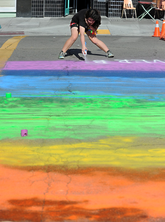 . Izzy Maturana, 16, of Berkeley, paints a crosswalk in rainbow colors on a closed street during a celebration of the Supreme Court\'s decision on Proposition 8 and the Defense of Marriage Act during an event held in Oakland, Calif., on Wednesday, June 26, 2013. The U.S. Supreme Court dismissed California\'s Proposition 8 and declared the 1996 Defense of Marriage Act unconstitutional. (Doug Duran/Bay Area News Group)