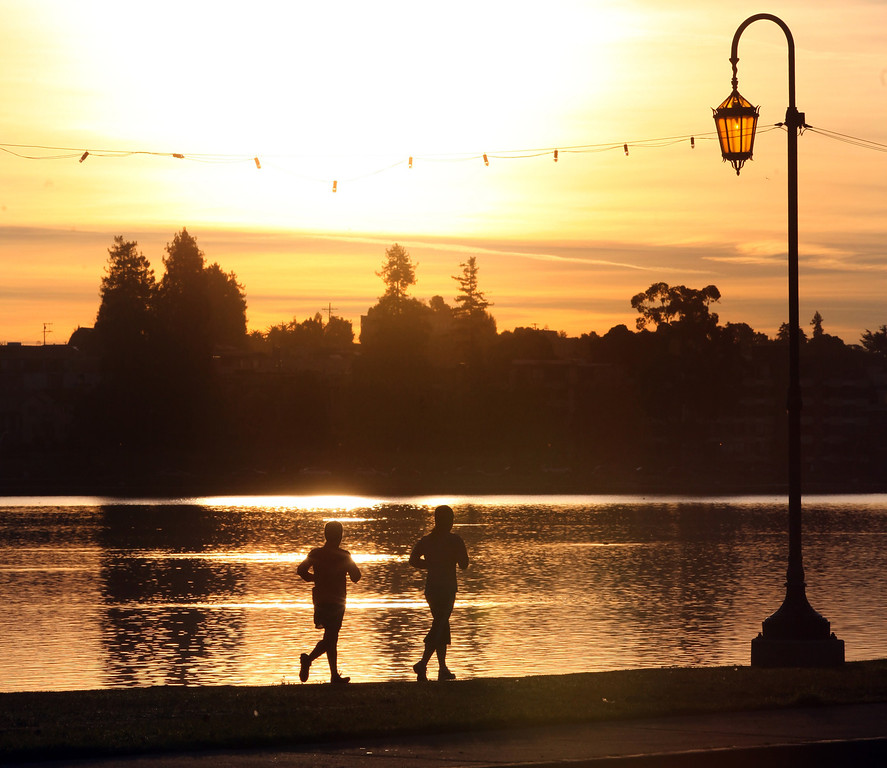 . Joggers brave the cold temperatures to jog around Lake Merritt  in Oakland,Calif., on Tuesday, Jan. 15, 2013 as the morning sun rises.  (Laura A. Oda/Staff)