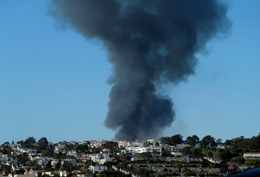 . A plume of smoke rises up over Potrero Hill from a fire burning in the Mission Bay neighborhood of San Francisco, Calif., Tuesday afternoon March 11, 2014. (Karl Mondon/Bay Area News Group)
