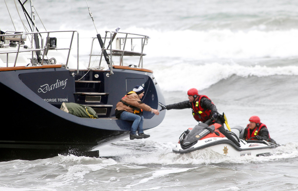 . Rescuers attempt to grab a woman off the back of the 82-foot-long sailboat, the Darling, stuck in the surf off Linda Mar Beach in Pacifica, Calif., Monday morning March 4, 2013. The boat had been reported stolen from a Sausalito marina earlier. The three people aboard were all rescued and arrested. (Karl Mondon Photo)