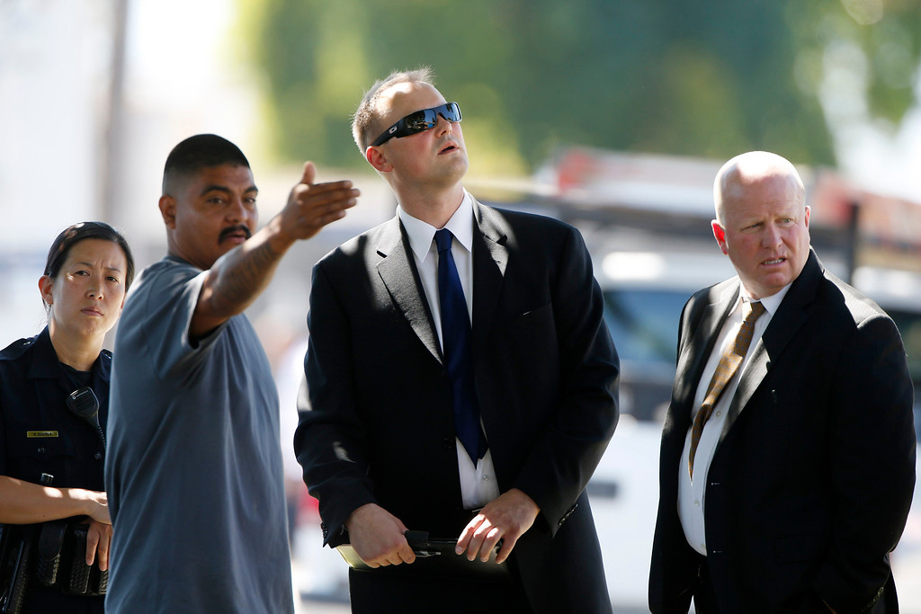 . San Jose resident Marco Padilla talks with San Jose State\'s Capt. Michael Barnes, center, and a San Jose Police detective, right, at the scene of  San Jose\'s 37th homicide at tennis courts parking lot at  San Jose State University in San Jose, Calif., on Sunday, Sept. 8, 2013. A body was found on the passenger side of an off-road vehicle.  (Josie Lepe/Bay Area News Group)