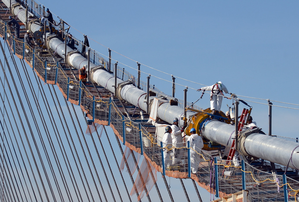 . Blue-suited iron workers and white-suited cable wrapping crew workers are high up the main suspension cable of the new Bay Bridge on Friday morning Nov. 2, 2012 in San Francisco, Calif. (Karl Mondon/Staff)