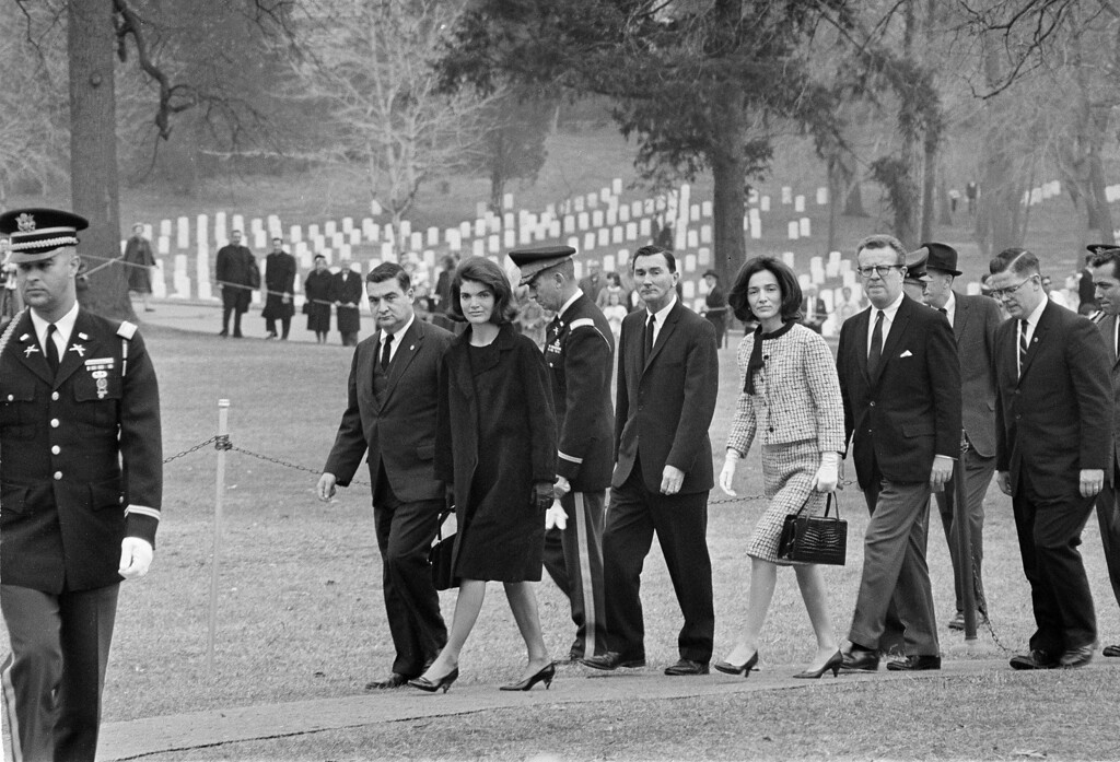 . Former first lady Jacqueline Kennedy walks toward the grave of slain President John F. Kennedy at Arlington National Cemetery, Arlington, Va., on Thanksgiving Day, Nov. 28, 1963. Walking beside Mrs. Kennedy is White House press secretary Pierre Salinger. Others are unidentified.   (AP Photo/Bob Schutz)