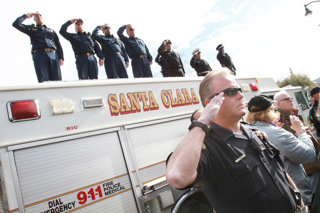 . Los Gatos police officer Leyton Howard and members of local fire departments salute while standing on the Main Street overpass in Los Gatos, Calif., as the funeral procession for two slain Santa Cruz police officers makes its way to San Jose\'s HP Pavilion, and the funeral, on March 7, 2013. (George Sakkestad/Bay Area News Group)