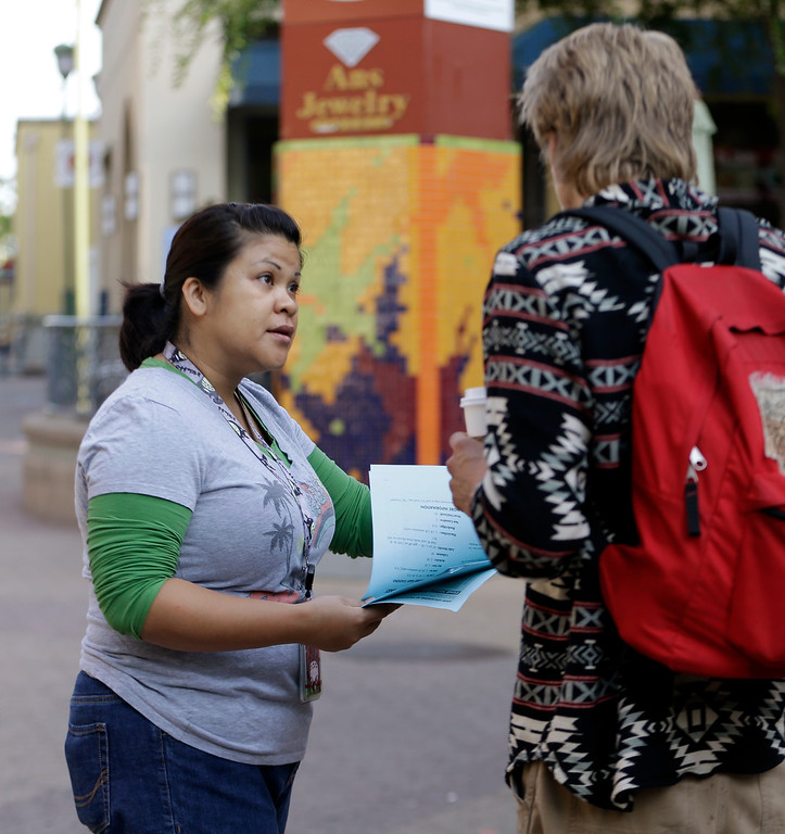 . Tina Ebojo, left, an employee of AC Transit, offers alternative travel information to a BART commuter who was unaware of a the strike Monday, July 1, 2013, in Oakland, Calif. (AP Photo/Ben Margot)