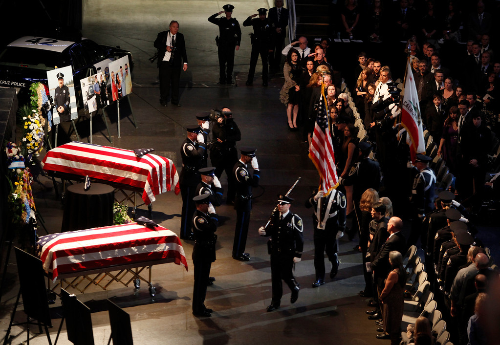 ". An honor guard marches up to the dual caskets of Santa Cruz police officers Sgt. ""Butch\"" Baker and Detective Elizabeth Butler at the start of a memorial service at the HP Pavilion on Thursday, March 7, 2013 in San Jose, Calif. The officers were killed during an ambush in Santa Cruz last week. (Karl Mondon/Staff)"