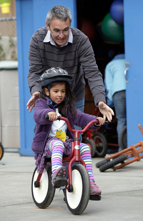 . Tim Dobbins, assistant teacher, helps Maddie Dhillon, 4, ride a two-wheeler at the Mountain View Parent Nursery School in Mountain View, Calif. on Friday, Feb. 8, 2013. The Mountain View-Whisman School District has decided that if parents hold back an eligible child from kindergarten, it will help evaluate those children for kindergarten-readiness the following year. Some will be sent to first grade rather than kindergarten. (Gary Reyes/ Staff)
