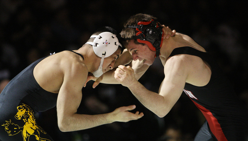 . Gilroy\'s Victor Olmos, left, battles Gunn\'s Eric Cramer in his victory in the 126 pound class during the CCS wrestling championships at Independence High School in San Jose, Calif. on Saturday, Feb. 23, 2013. (Jim Gensheimer/Staff)
