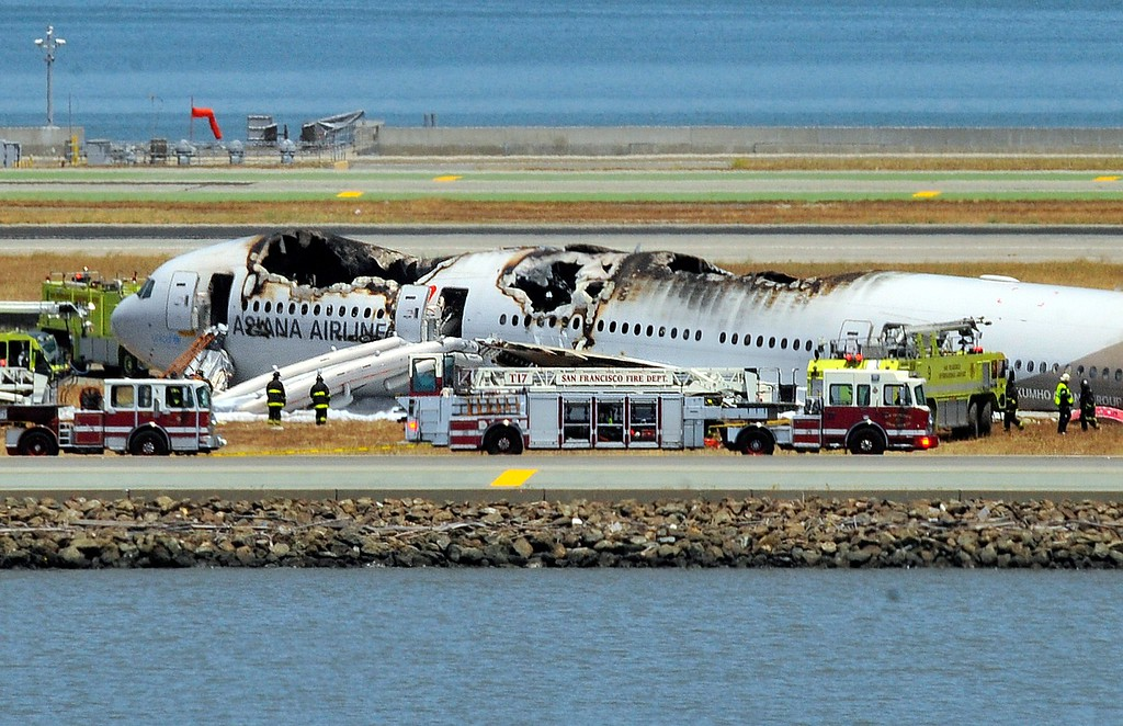. An Asiana Airlines Boeing 777 is seen on the runway at San Francisco International Airport after crash landing on July 6, 2013. There were no immediate reports of casualties and one apparent survivor tweeted a picture of passengers fleeing the plane. Video footage showed the jet, Flight 214 from Seoul, on its belly surrounded by firefighters. (Josh Edelson/AFP/Getty Images)