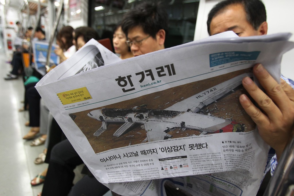 ". A passenger reads a newspaper reporting about Asiana Airlines flight 214 which took off from Seoul and crashed while landing at San Francisco International Airport  on Saturday, on a subway train in Seoul, South Korea, Monday, July 8, 2013.  The headline reads ""Asiana did not notice anything wrong until the accident happened.\"" (AP Photo/Ahn Young-joon)"