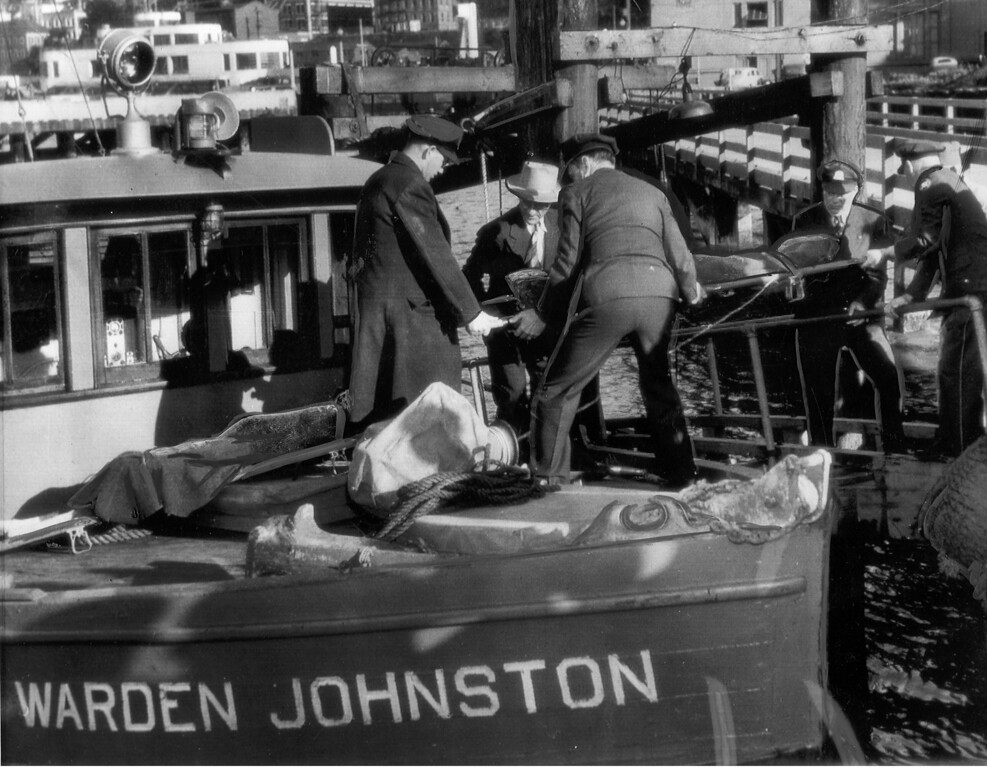 . One of three bodies of convicts who died in rioting on Alcatraz is moved ashore by police and prison officials from the deck of the prison boat Warden Johnston en route to the San Francisco coroner\'s office. (AP Photo/Tribune archives)